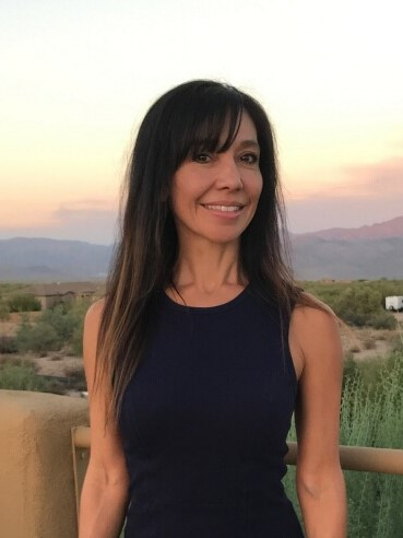 Female realestate agent wearing black clothing smiling in front of a desert landscape